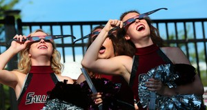 Saluki cheerleaders try out eclipse glasses that they were giving out to visitors to Saluki Stadium on the campus of Southern Illinois University Carbondale, Ill., on Monday, Aug. 21, 2017.