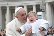 Pope Francis stops to kiss small boy dressed in papal style