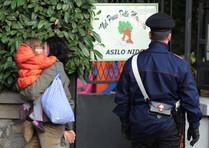 I carabinieri davanti l'asilo con una mamma e il suo bambino