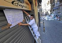 Il titolare del ristorante fissa sulla serranda il cartello con cui ha deciso di chiudere l'attivita' per la presenza dei cumuli di rifiuti