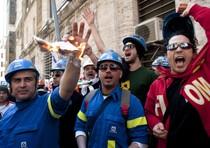 Operai bruciano le tessere elettorali durante la manifestazione degli operai dell'Alcoa sotto il ministero
