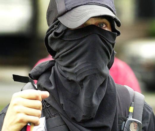 Un manifestante con lil caratteristico abbigliamento nero, il viso coperto e la trasmittente