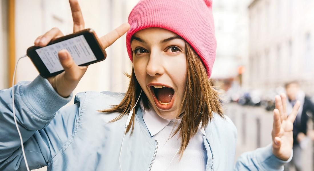 Cappello con pon pon, una ragazzina ascolta musica dal cellulare foto iStock. © Ansa