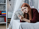 Una ragazza preoccupata guarda il telefonino foto iStock. (ANSA)
