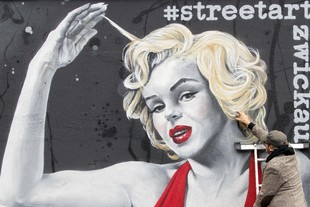 German street art artist TASSO (Jens Mueller) completes his new work, a graffito wall painting showing Hollywood star Marilyn Monroe during the official opening in Zwickau, eastern Germany, Saturday, Oct. 7, 2017.