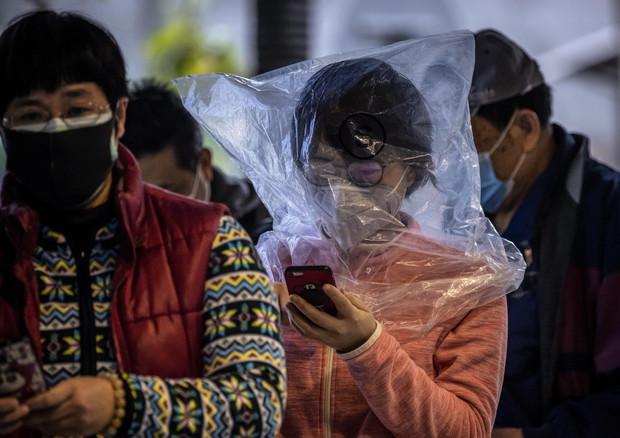 Cinesi con la mascherina per proteggersi dal virus © EPA