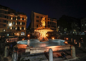 The Tritone's Fountain is illuminated in orange
