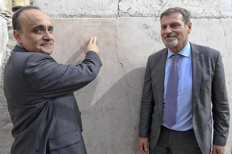 Il ministro Alberto Bonisoli con il sovrintendente Massimo Osanna mostrano la scritta su un muro degli scavi di Pompei /FOTO CIRO FUSCO © ANSA