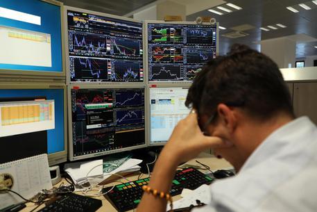 Un operatore di Borsa di una banca davanti ai monitor © ANSA