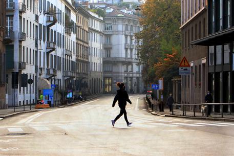 Una ragazza in una strada vuota a Milano © ANSA