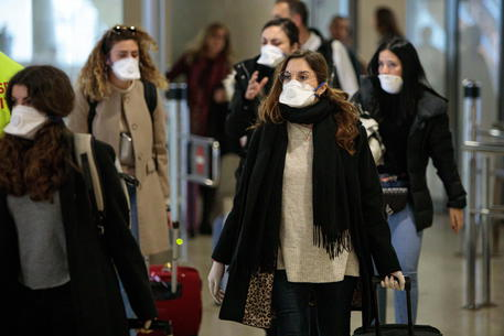 Viaggiatori con le mascherine all'aeroporto di Valencia © EPA