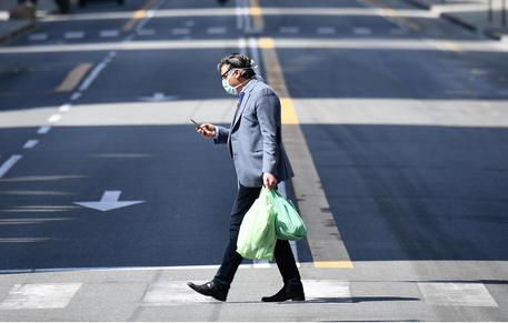 Un uomo cammina in una strada deserta guardando il telefono © ANSA
