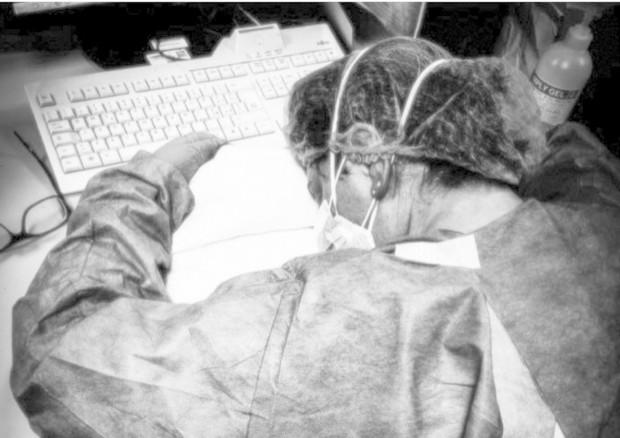 Un'infermiera stravolta dopo il turno di lavoro © ANSA